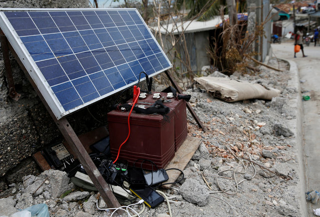 Mobile phones are being charged through solar panels after Hurricane Matthew passes in Jeremie, Haiti, October 9, 2016. (Photo by Carlos Garcia Rawlins/Reuters)