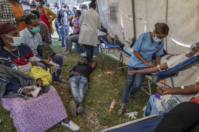 A man lies down after giving blood at a blood drive in support of the country's military, at a stadium in the capital Addis Ababa, Ethiopia Thursday, November 12, 2020. (Photo by Mulugeta Ayene/AP Photo)