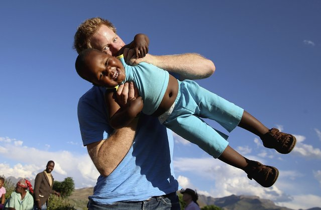 Britain's Prince Harry swings three-year-old orphan boy Lerato, in this photograph taken with the help of three-year-old blind girl Karabo, during a visit to Phelisanong Children's Home in Maseru December 6, 2014. Prince Harry was visiting Lesotho to see the work of his charity Sentebale, which provides healthcare and education to vulnerable children. (Photo by Chris Jackson/Reuters)