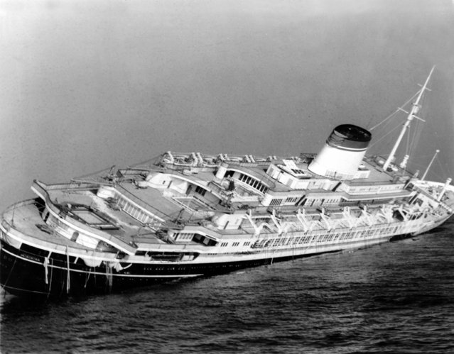 The Italian luxury liner Andrea Doria keels far over to starboard before sinking 225 feet to the bottom of the Atlantic 45 miles off Nantucket Island, Ma., July 26, 1956. The Andrea Doria was struck broadside by the Swedish-American liner Stockholm in heavy fog July 25 at 11:10 p.m.. (Photo by John Rooney/AP Photo)