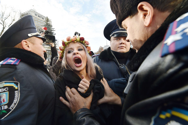 Ukrainian police detain an activist of the feminist movement Femen as she shouts slogans during a demonstration calling for gay rights outside the Ukrainian parliament in Kiev on November 12, 2015. Ukraine's parliament are due to hold a vote to adopt a ban on anti-gay discrimination in the workplace – a law needed to secure visa-free travel to most EU nations. (Photo by Sergei Supinsky/AFP Photo)