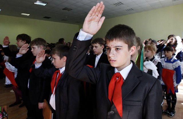 Children, wearing red neckerchiefs, a symbol of the Young Pioneer Organisation, salute during a ceremony for the inauguration of 55 newly adopted members on the day of its anniversary at school-lyceum number 12 in Russia's Siberian city of Krasnoyarsk May 19, 2011. (Photo by Ilya Naymushin/Reuters)
