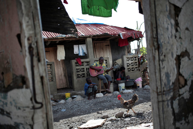 A rooster passes next to a man playing the guitar after Hurricane Matthew in Damassins, Haiti, October 22, 2016. (Photo by Andres Martinez Casares/Reuters)