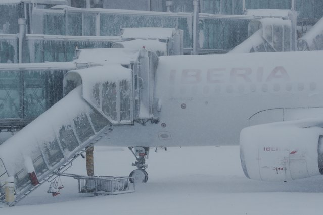 A parked plane is covered with snow at Adolfo Suarez Barajas airport, which is suspending flights due to heavy snowfall in Madrid, Spain, January 9, 2021. (Photo by Susana Vera/Reuters)