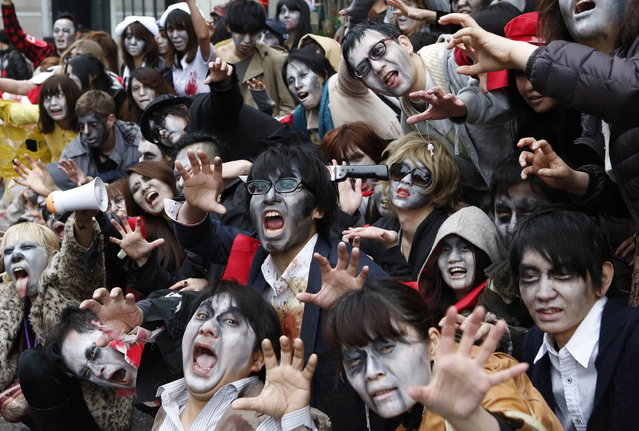People, dressed as zombies, pose for photos after the Roppongi Zombie Walk in Tokyo March 31, 2013. (Photo by Yuya Shino/Reuters)