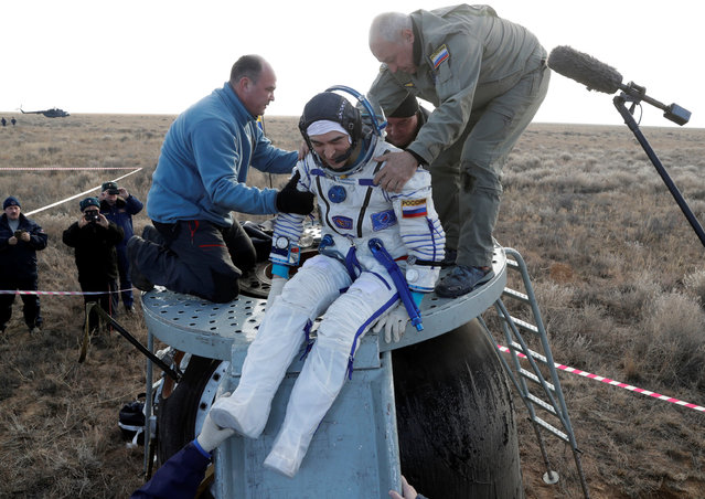 Russian space agency rescue team helps International Space Station (ISS) crew member Anatoly Ivanishin of Russia to get from the capsule shortly after the landing of the Russian Soyuz MS space capsule near the town of Dzhezkazgan (Zhezkazgan), Kazakhstan, October 30, 2016. (Photo by Dmitri Lovetsky/Reuters)