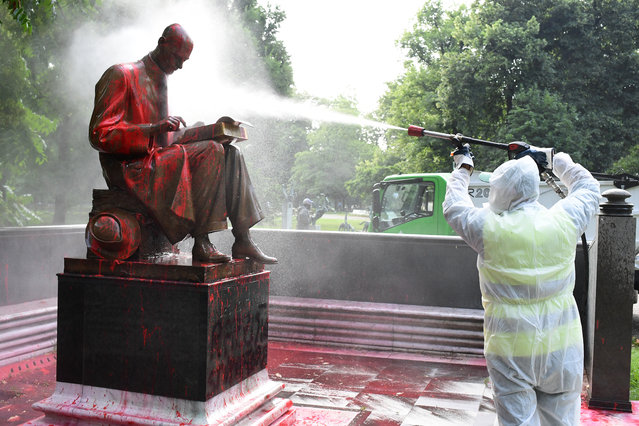 """A municipal employee cleans a statue of a famous Italian journalist Indro Montanelli on June 14, 2020 in a Milan public square, a day after it was defaced, stained with red paint and tagged with the inscription """"racist, rapist"""". It is the first statue to be damaged in Italy since the wave of protests around the world triggered by the death of George Floyd in the US. (Photo by Miguel Medina/AFP Photo)"""