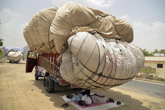 Indian men sleep in the shadow of an overflowing cloth container of hay, to be used as animal fodder, on a truck on a hot summer day in Ajmer in the western state of Rajasthan on May 30, 2018. (Photo by Shaukat Ahmed/AFP Photo)