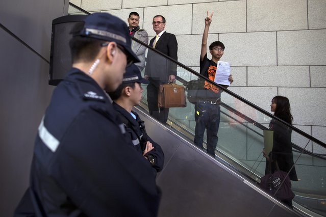 Hong Kong student leader Joshua Wong, 18, gestures to supporters as he arrives at the police headquarters in Hong Kong January 16, 2015. Hong Kong student leaders, including Wong, reported to a police station to face arrest for their leadership roles in the months-long pro-democracy protests also known as the Umbrella Movement. (Photo by Tyrone Siu/Reuters)