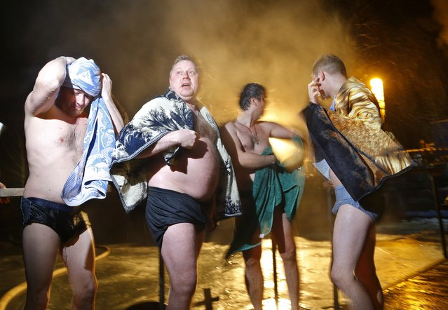Belarusians warm themselves after swimming in the ice cold water of a lake on the eve of Russian Orthodox Epiphany in Minsk, Belarus, late Sunday, January 18, 2015. (Photo by Sergei Grits/AP Photo)