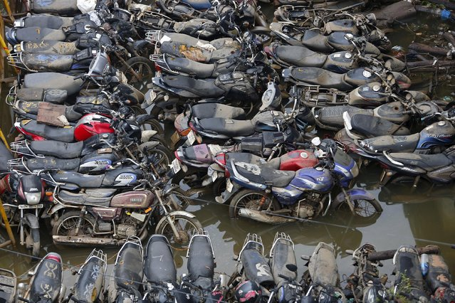 Motorcycles stand in a flooded parking area in Chennai, India, December 5, 2015. (Photo by Anindito Mukherjee/Reuters)