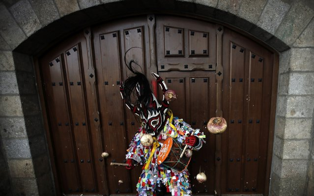 A Jarramplas stands against a wooden door as turnips are thrown at him by revellers during the Jarramplas traditional festival in Piornal, southwestern Spain, January 20, 2015. (Photo by Sergio Perez/Reuters)