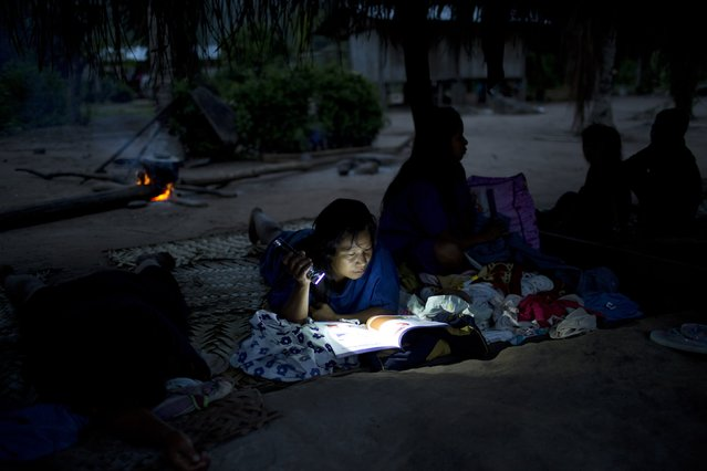 In this November 19, 2015 photo, Elva Yumiquiri reads a manual from health workers to prepare nutritional meals for her children, before the start of a meeting organized by the government food program targeting public schools, in Pichiquia, an Ashaninka indigenous community in Peru's Junin region. Yumiquiri uses a flashlight to illuminate the manual because her community has no electricity. (Photo by Rodrigo Abd/AP Photo)