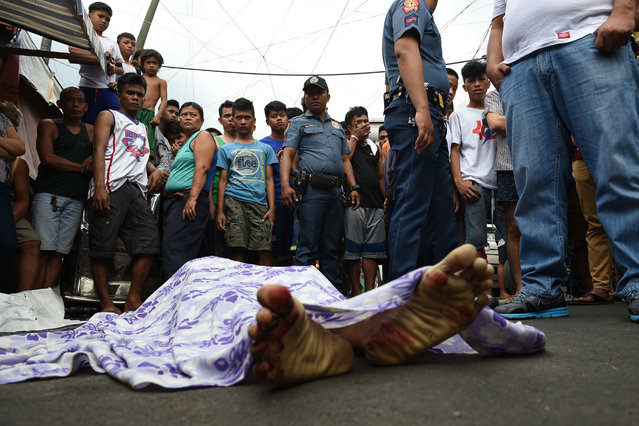 Residents and policemen gather over the body of a suspect killed during an anti-drug operation at an informal settlers' area near a port in Manila on November 10, 2016. Philippine President Rodrigo Duterte's war on drugs and other crimes took he office on June 30 has claimed 4,447 lives, according to official figures made available by police on November 10. (Photo by Ted Aljibe/AFP Photo)