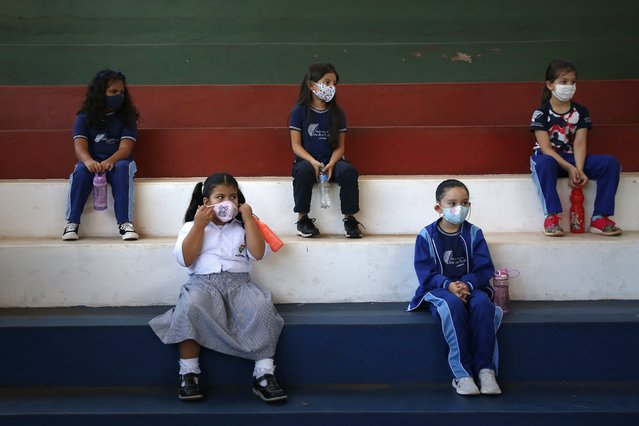 First-grade students wear masks and socially distance in the gym during class at San Juan Bautista technical school in Lambare, Paraguay, Wednesday, February 17, 2021. Some private primary schools opened in-person classes this week with strict health security protocols amid the COVID-19 pandemic. (Photo by Jorge Saenz/AP Photo)