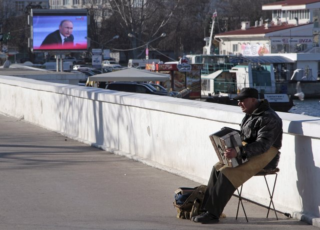 A man plays the accordion, with a screen showing Russian President Vladimir Putin's annual end-of-year news conference seen in the background, on an embankment of the Black Sea port of Sevastopol, Crimea, December 17, 2015. (Photo by Pavel Rebrov/Reuters)