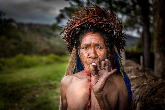 Dani tribeswoman smokes a cigarette and shows her amputated fingers in, Western New Guinea, Indonesia, August 2016. (Photo by Teh Han Lin/Barcroft Images)