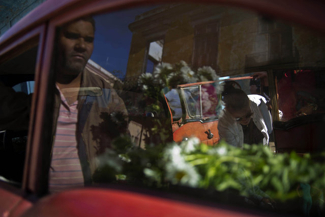 In this Thursday, January 29, 2015 photo, self-employed flower vendor Yaima Gonzalez, 33, right, sells flowers from a 1957 parked Buick she has rented for the day, in Havana, Cuba. (Photo by Ramon Espinosa/AP Photo)