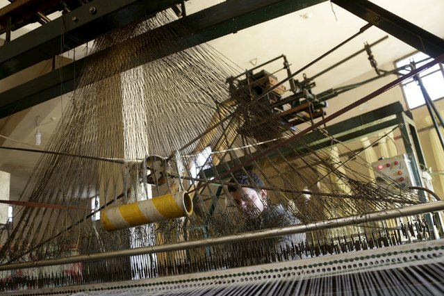 A man operates a machine inside a mat factory in the rebel-controlled area of Maarshureen town in Idlib province, Syria, December 22, 2015. (Photo by Khalil Ashawi/Reuters)