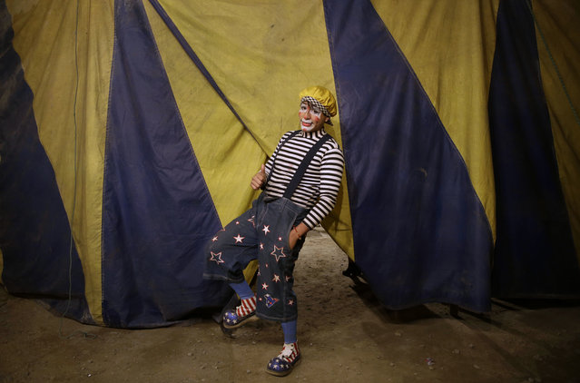 """In this July 8, 2018 photo, Santiago Astopilco, dressed as his clown personality """"Vaguito"""" poses for a portrait behind the Tony Perejil circus tent set up in the shantytown of Puente Piedra, before the start of the show on the outskirts of Lima, Peru. Circus workers earn a percentage of ticket sales, sell candy and hotdogs on sticks to make extra money, and travel year-round from town to town, with July being the high season in the capital. (Photo by Martin Mejia/AP Photo)"""