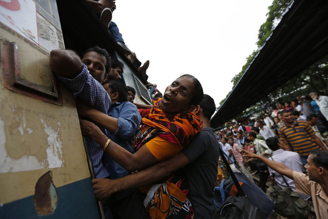 Passengers spill out from the train door as they travel aboard an overcrowded train at a railway station in Dhaka August 8, 2013. Millions of residents in Dhaka are travelling home from the capital city to celebrate the Muslim Eid al-Fitr holiday, which marks the end of the fasting month of Ramadan. (Photo by Andrew Biraj/Reuters)