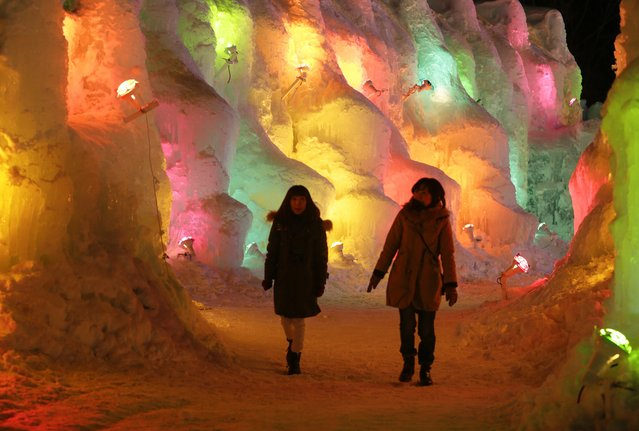 Visitors walk through colorful illuminated ice structures at the Shikotsukoonsen Ice Festival in Shikotsukoonsen, outskirts of Chitose, northern Japan, February 6, 2015. The lowest temperature at the lakeside town was minus 16 degrees Celsius on February 6. The ice festival is held from January 30 to February 33. (Photo by Kimimasa Mayama/EPA)