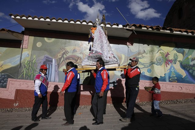 """In this Sunday, August 5, 2018 photo, """"cargadores"""" or male carriers walk with a statue of Our Lady of Copacabana belonging to resident Libia Espinoza, in a religious procession honoring the Bolivian virgin, in Cuzco, Peru. Unlike many of the regional feast day celebrations dating back hundreds of years, this one, initiated by Espinoza, is marking its tenth year. (Photo by Martin Mejia/AP Photo)"""