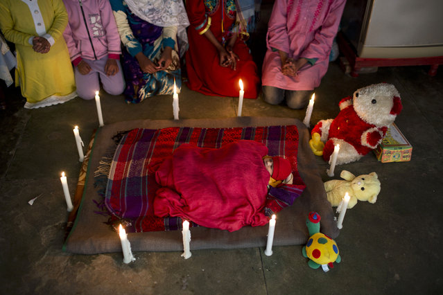 In this Sunday, February 1, 2015 photo, a 5 day-old Christian infant who was named Ashber following his baptism ceremony, is celebrated by relatives at the family's home, in Rawalpindi, Pakistan. Many Christians face discrimination and eke out a living by holding low-paying jobs. However, they've carved out their own lives in a country that faces near-daily attacks by Islamic extremists. (Photo by Muhammed Muheisen/AP Photo)