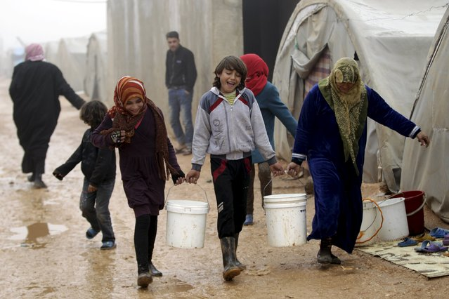 Internally displaced people carry buckets of water as they walk during the cold weather in Jerjnaz camp, in Idlib province, Syria, January 5, 2016. (Photo by Khalil Ashawi/Reuters)