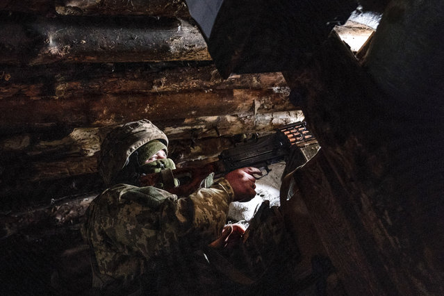 In this March 5, 2021, file photo, a Ukrainian serviceman keeps ready a machine gun in his shelter near the front-line town of Krasnohorivka, eastern Ukraine. Tensions are rising over the conflict in eastern Ukraine, with growing violations of a cease-fire and a massive Russian military buildup near its border with the region. (Photo by Evgeniy Maloletka/AP Photo/File)