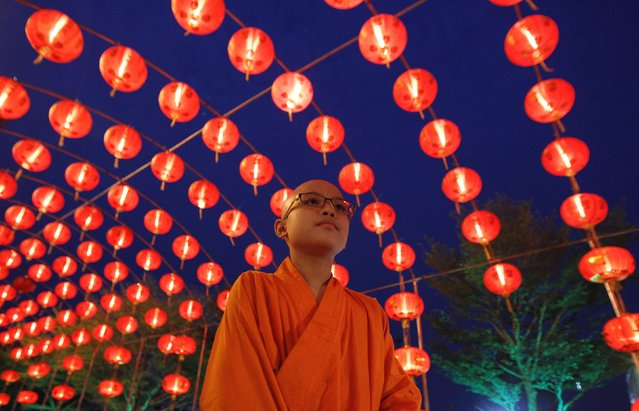 A Chinese Buddhist monk walks under decorations at a temple, ahead of the Chinese Lunar New Year celebrations in Nonthaburi province, on the outskirts of Bangkok February 18, 2015. (Photo by Chaiwat Subprasom/Reuters)