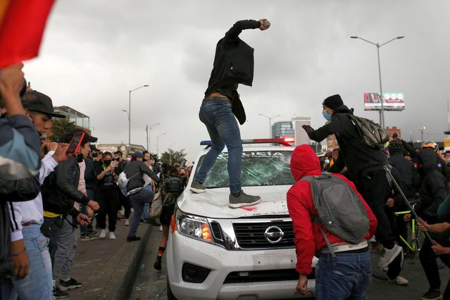 A demonstrator prepares to throw a stone at a police vehicle during a protest against the tax reform of President Ivan Duque's government in Bogota, Colombia on April 28, 2021. (Photo by Luisa Gonzalez/Reuters)