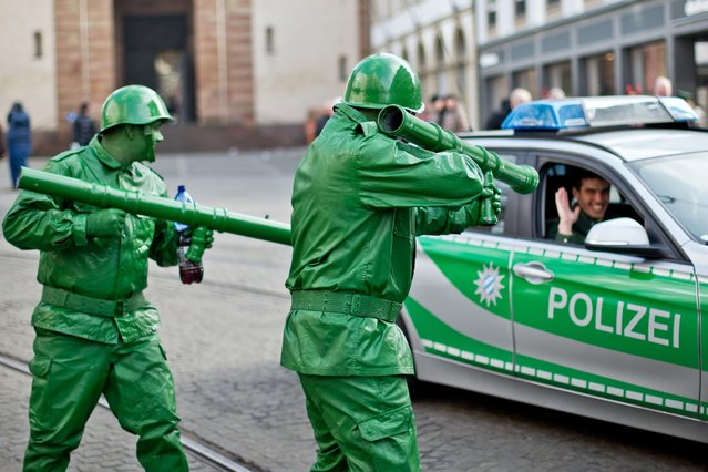 "Two revelers dressed as toy soldiers gesture toward a police officer in a patrol car during the traditional carnival parade in Wuerzburg, Germany, 15 February 2015. Under the motto ""Carnival Parade is cool"" about 160 groups with over 3,000 members took part in one of the biggest carnival parades in southern Germany. (Photo by Daniel Karmann/EPA)"