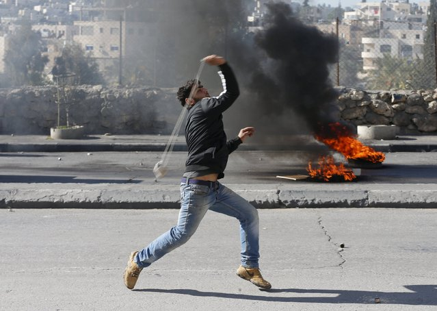 A Palestinian protester uses a sling to hurl stones towards Israeli troops during clashes in the West Bank city of Bethlehem January 13, 2016. (Photo by Ammar Awad/Reuters)