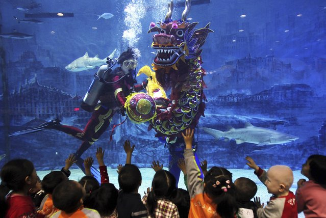 A diver performs a dragon dance for children at Beijing Aquarium, February 16, 2015. (Photo by Reuters/China Daily)