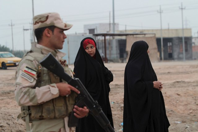 Iraqi women walk past a checkpoint in Basra province, Iraq on January 15, 2016. (Photo by Essam Al-Sudani/Reuters)