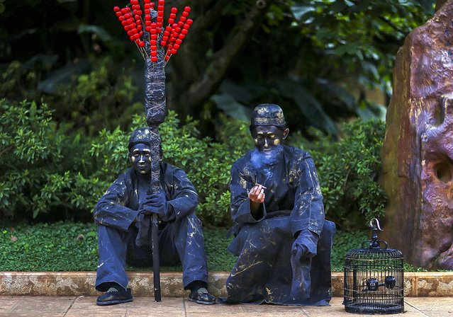 Street artists dressed as bronze statues smokes as he sits next to his partner during a break in their performance in Kunming, Yunnan province, on October 1, 2013. (Photo by Wong Campion/Reuters)