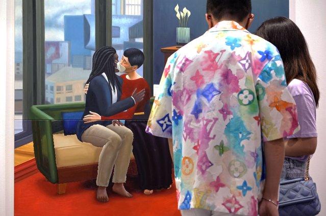 "Two visitors look at an artwork ""Home Sweet Home: Pandemic Love 1"" created by Hong Kong artist Mak Ying Tung at Art Basel in Hong Kong Wednesday, May 19, 2021. (Photo by Vincent Yu/AP Photo)"