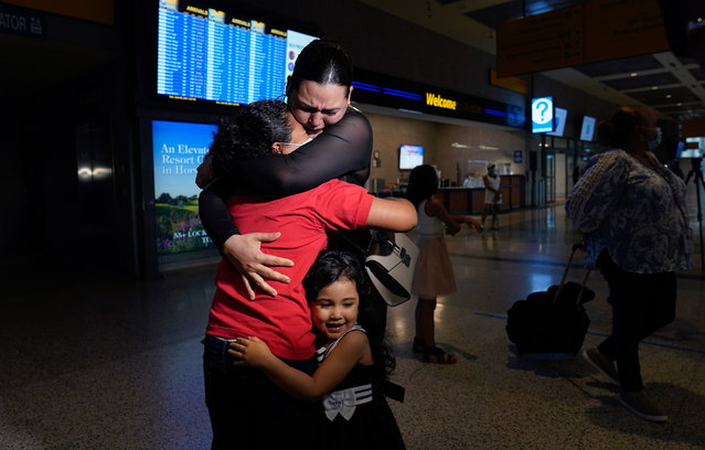 Emely, left, is reunited with her mother, Glenda Valdez and sister, Zuri, at Austin-Bergstrom International Airport, Sunday, June 6, 2021, in Austin, Texas. It had been six years since Valdez said goodbye to her daughter Emely in Honduras. Then, last month, she caught a glimpse of a televised Associated Press photo of a little girl in a red hoodie and knew that Emely had made the trip alone into the United States. On Sunday, the child was returned to her mother's custody. (Photo by Eric Gay/AP Photo)
