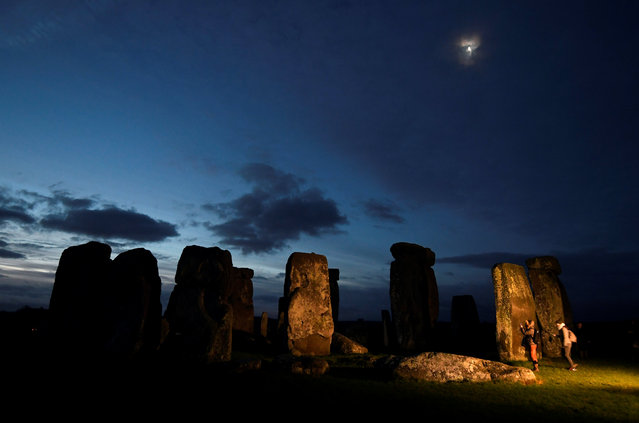 Visitors take photos amongst the prehistoric stones of the Stonehenge monument at dawn on Winter Solstice, the shortest day of the year, near Amesbury in south west Britain, December 21, 2016. (Photo by Toby Melville/Reuters)