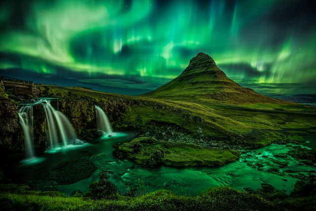 """A burst of the aurora borealis over Kirkjufell, taken in September 2016. This shot has been a holy grail for me and was finally captured after many trips"". MICK RYAN, JUDGE: Iceland is a hotspot for aurora photography and this composition of the symmetric, free-standing Kirkjufell and the trident waterfall is much-sought after. If you can time your visit when the aurora ""kp"" index is high and know the settings for nighttime aurora images, you may end up with a beautiful photograph like this. (Photo by DB/The Guardian)"""