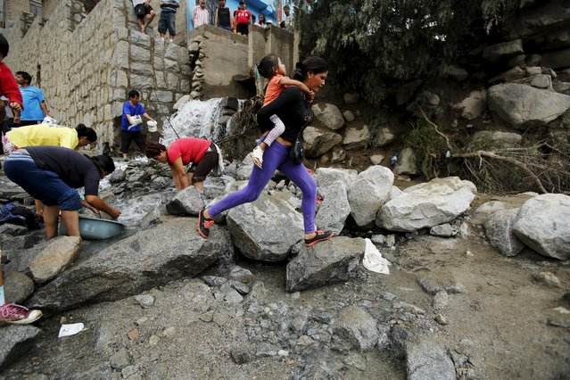 A woman carring a girl crosses a flooded street after a massive landslide in Chosica, March 24, 2015. (Photo by Mariana Bazo/Reuters)