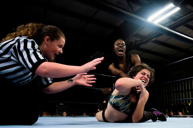Professional wrestler Gia Scott (C) screams as she puts professional wrestler Aria Palmer (R) into a choke hold during Autumn Armageddon 2018 in Galena, Maryland on October 6, 2018. (Photo by Jim Watson/AFP Photo)