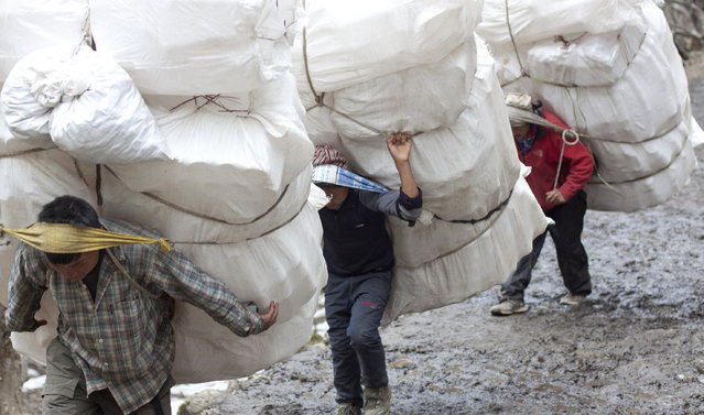 In this Monday, March 23, 2015 photo, porters carry loads of plastic bottles towards a mineral water factory at Pangboche, a village inhabited by mainly Sherpas, in Nepal. (Photo by Tashi Sherpa/AP Photo)