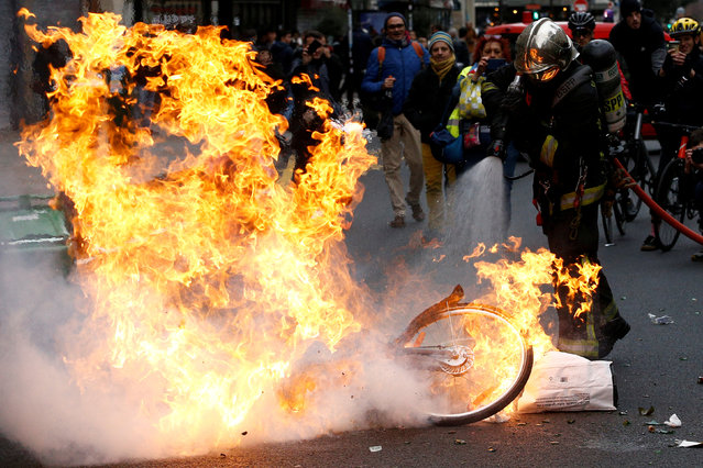"A fireman extinguishes a burning bicycle during clashes with yellow vests protesters as part of a national day of protest by the ""yellow vests"" movement in Paris, France, December 8, 2018. (Photo by Stephane Mahe/Reuters)"