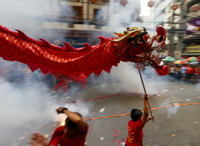 Dragon and lion dancers perform amidst exploding firecrackers in celebration of the  Chinese Lunar New Year Monday, February 8, 2016 at Manila's Chinatown district in Manila, Philippines. (Photo by Bullit Marquez/AP Photo)