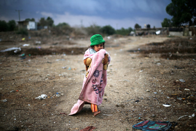 A Palestinian girl, wrapped in a blanket, walks outside her family dwelling on a rainy day in Khan Younis in the southern Gaza Strip December 14, 2016. (Photo by Ibraheem Abu Mustafa/Reuters)