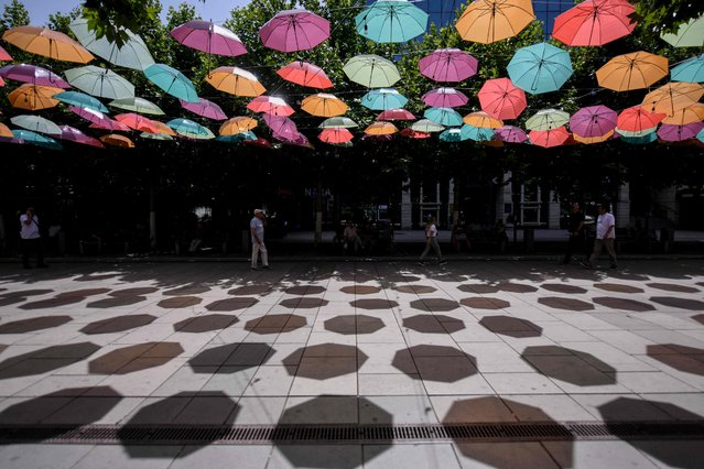 Pedestrians walk under colorful umbrellas hanged over Mother Teresa square in Pristina on July 14, 2021 as temperatures exceed 37 degrees celsius in Kosovo. (Photo by Armend Nimani/AFP Photo)