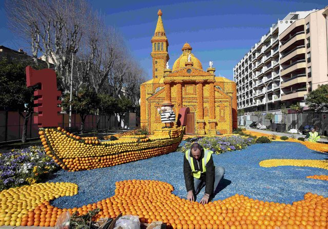 "A workers puts the final touch to a replica of a gondola and a Venetian palace made with lemons and oranges which shows a scene of the movie ""Morte a Venezia"" (Death in Venice) during the Lemon festival in Menton, southern France, February 10, 2016. (Photo by Eric Gaillard/Reuters)"