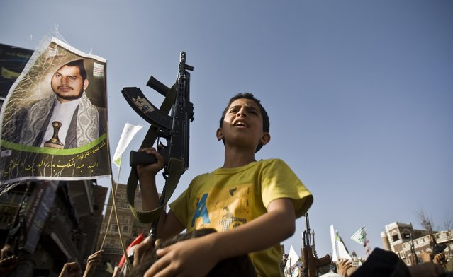 A boy holds a weapon while Shiite rebels known as Houthis protest against Saudi-led airstrikes, during a rally in Sanaa, Yemen, Wednesday, April 1, 2015. The poster shows Yemen's Houthi rebel leader Abdul-Malik al-Houthi. (Photo by Hani Mohammed/AP Photo)